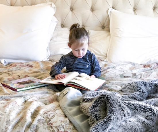 little girl reading tufted headboard fur blanket